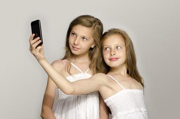 Two young girl taking a selfie, kids taking a photo, having fun
