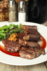 Steak with wine sauce on plate on table close up
