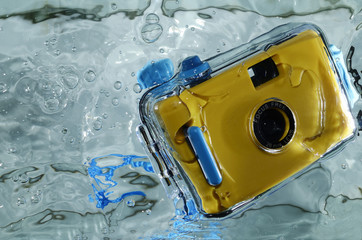 Photo of yellow waterproof camera in water with splash.