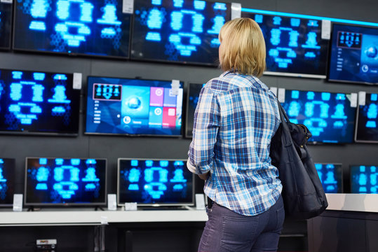 Blonde girl looks at TVs in supermarket