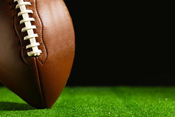 American football on green grass, on black background