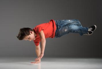 little break dancer showing his skills on grey background.
