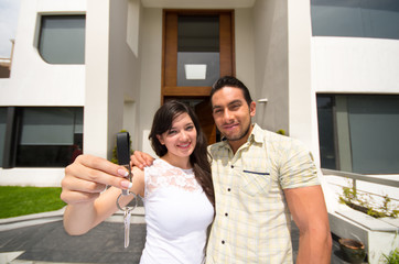 happy couple holding key to their new house