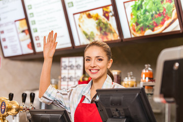 Restaurant worker at cashier smiling at work place.