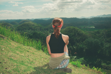 Young woman sitting on a hill and admiring view