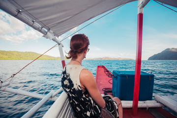 Woman on boat approaching tropical island
