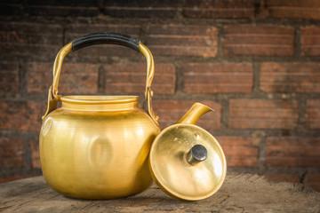 brass kettle brick background