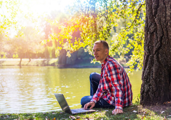 Young man with his laptop in city park outdoor