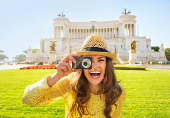 Smiling young woman taking photo on piazza venezia in rome