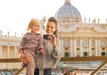 Mother and baby girl checking photos in camera in Vatican