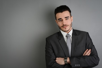 portrait of young business man posing in front of gray wall