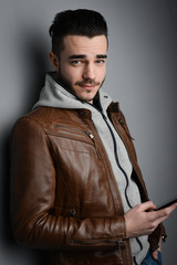 handsome young trendy man in a brown leather jacket