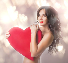 Beautiful girl with big heart in hands