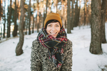 Young hipster woman in winter forest having fun