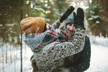 Young hipster couple having fun in winter forest