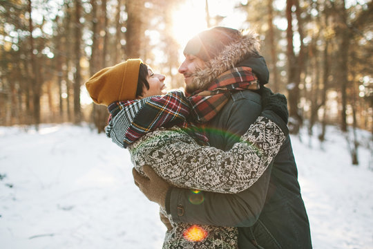 Young hipster couple hugging each other in winter forest