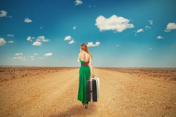 woman walking through desert talking on phone carrying suitcase