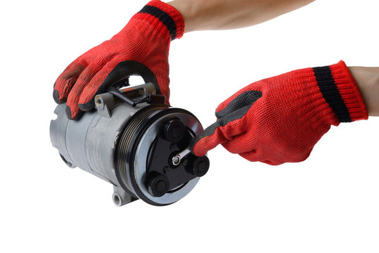 car mechanic hand use wrench to fix car air compressor on white