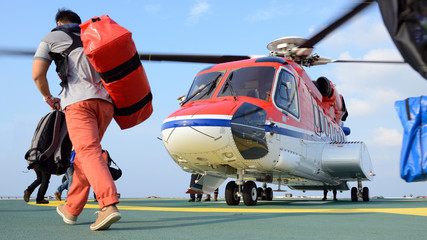 Foto auf Acrylglas Hubschrauber passenger carry his baggage to embark helicopter at oil rig plat