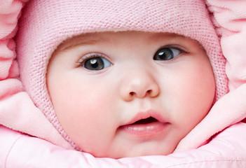 Beautiful baby in a pink hat. Winter season