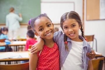 Cute pupils smiling at camera in classroom