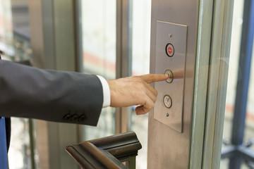 Businessan pressing elevator button