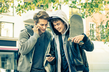 Young hipster best friends brothers having fun with smartphone