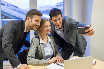Three business people taking Selfie in the office