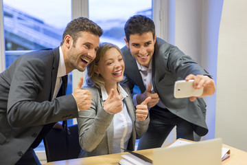 Three business people make Selfie in the office. The Thumbs up