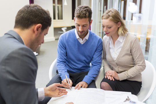 Couple real-estate agent for house investment. Signing contract