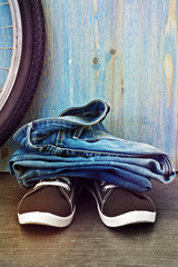 Jeans and sneakers on a background of blue wooden fence
