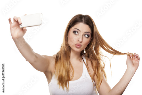 """Attractive young woman is taking a selfie"" Стоковая фотография и роялти-фри изображение на Fotolia.ru - Pic 77548385"
