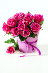 Bunch of pink roses in pink vase copy space background
