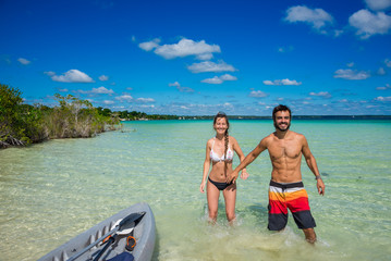 Beautiful couple in love kayaking at tranquil Bacalar lake.