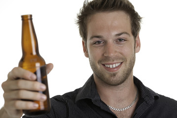Casual young man holding bottle of beer, smiling. Isolated on