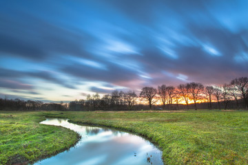 Wall Mural - Long Exposue Sunset with Blurred Clouds over River Landscape