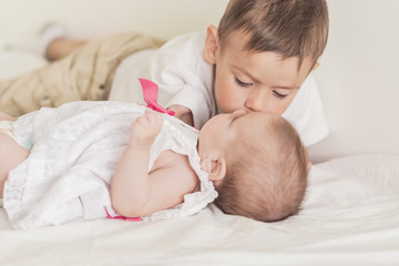 Little Caucasian Boy Kissing His Newborn Sister. Indoors Shot.