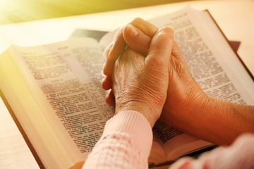 Hands of old woman with Bible on table, close-up