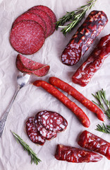 Fototapete - Assortment of sausages on sheet of paper background