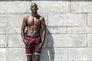 Fit muscular african american male model aganist  wall
