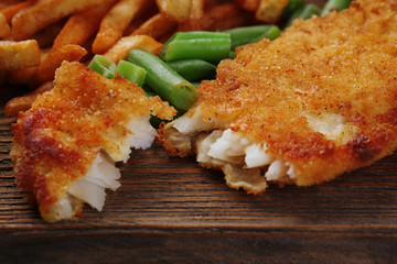 Breaded fried fish fillet and potatoes with asparagus