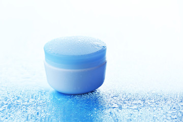 Cosmetic cream on blue background with water drops