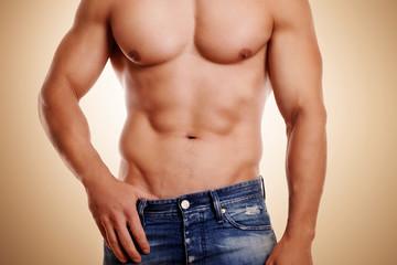 schöner Männerkörper vor beigen Hintergrund