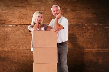 Wall Mural - Composite image of happy couple leaning on pile of moving boxes