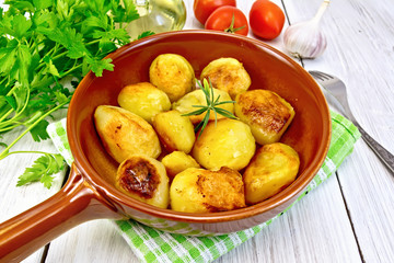 Potatoes fried in ceramic pan on light board