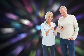 Composite image of happy mature couple using their smartphones