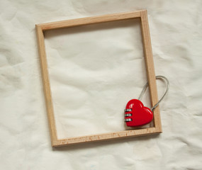 wooden frame and red metal lock on paper background
