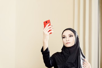 Beautiful Muslim woman is making a Selfie
