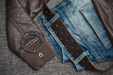 jeans with a leather belt, leather jacket, jewelry bracelet