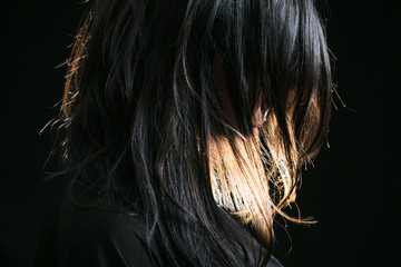Young woman with straight hair on dark background